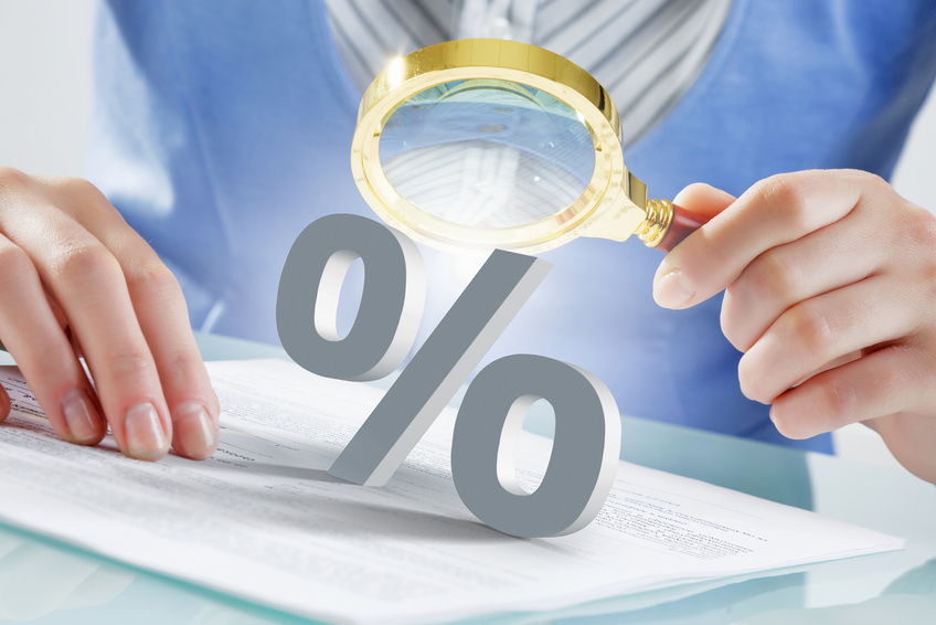 Close view of businesswoman looking at percentage sign with magnifier