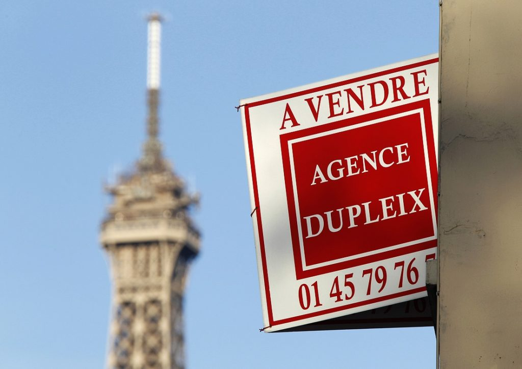 "A ""For Sale"" sign hangs outside an apartment on a building near the Eiffel Tower in Paris"